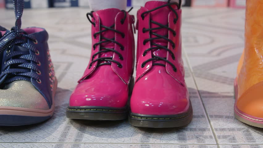 Child Trying On New Pink Combat Boots For Junior Girls In Children