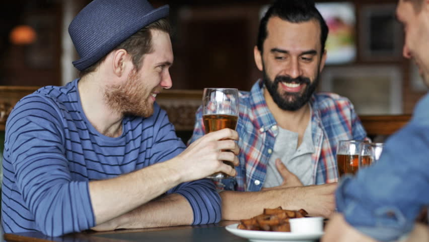 people, leisure, friendship and celebration concept - happy male friends drinking beer, eating bread snack and clinking glasses at bar or pub