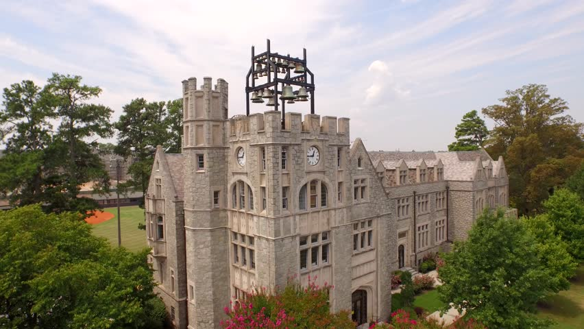 Aerial shot circling around a clock and bell tower with a carillon on top of a classic architecture style building at historic Oglethorpe University in Atlanta