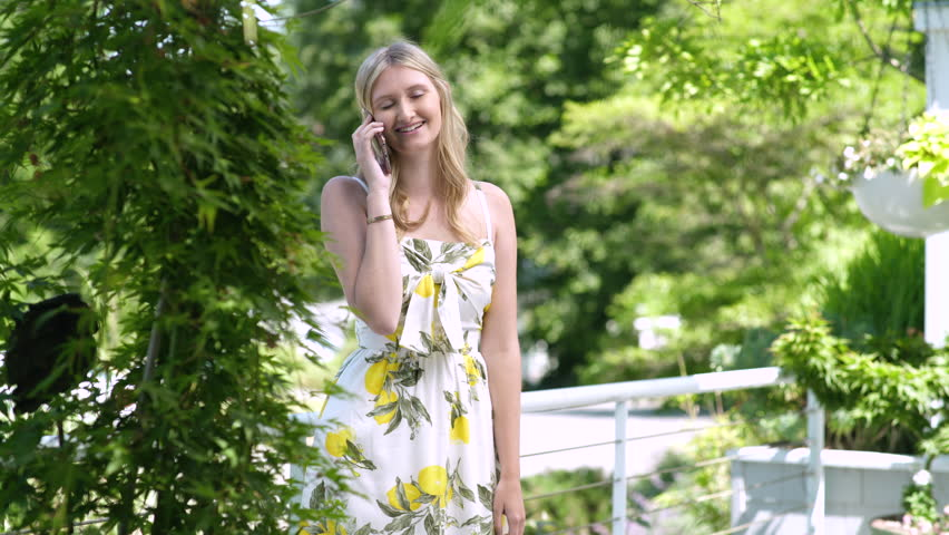 Young woman wearing sundress talking on smart phone