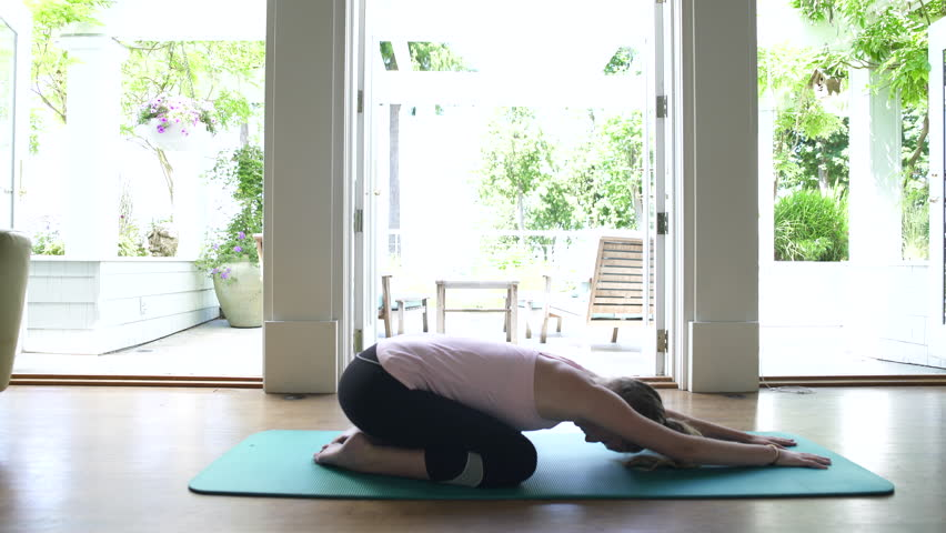 Young woman doing yoga by window, high angle view