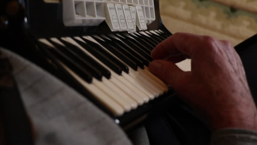 Playing the accordion. Hands playing music on a key board shot over the shoulder.