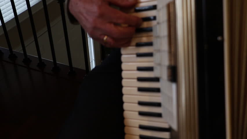 Musical instrument being played by an older man. Accordion keys being played.