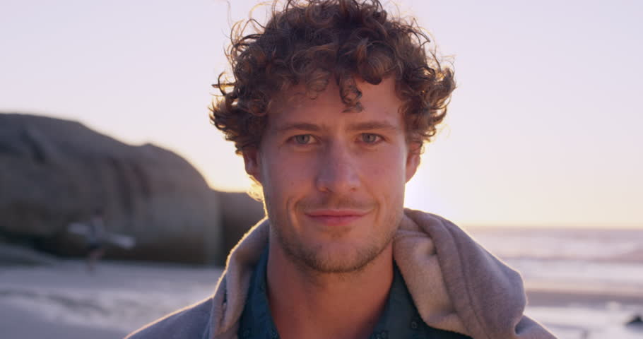 Portrait of attractive man smiling on beach at sunset in slow motion RED DRAGON