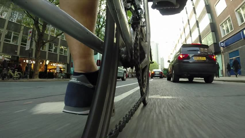 LONDON, SUMMER 2014 - A cyclist rides down the street on his way to work. Cycling in London can be dangerous with more fatalities all the time so he must swerve to avoid traffic