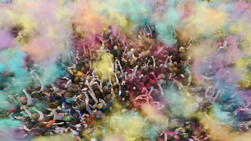 Russia, Chelyabinsk, 13 June 2015: Aerial flight above dancing crowd on Holi Festival Of Colors. Crowd of people colored powder and having fun.  #10425908