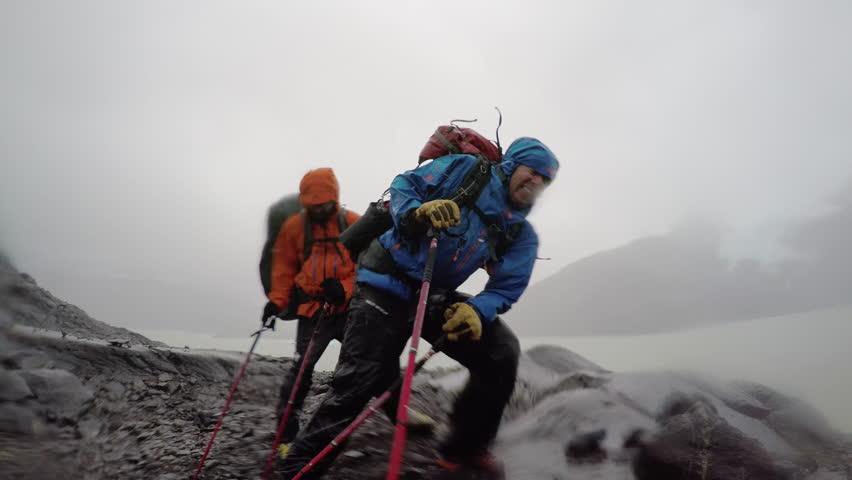 4k Adventure men fighting wind rain storm