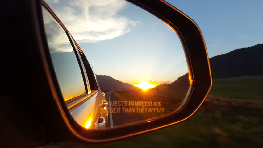 SANPETE COUNTY. UTAH - JUNE 2015: A beautiful orange and yellow sunset glows in the rear view mirror of an eastbound auto as it drives through a low mountain pass   Shutterstock HD Video #10530941