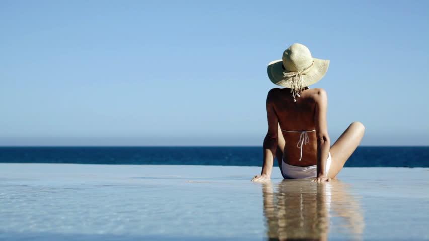 Sexy woman in summer hat and bikini sitting in infinity pool and taking sunbath
