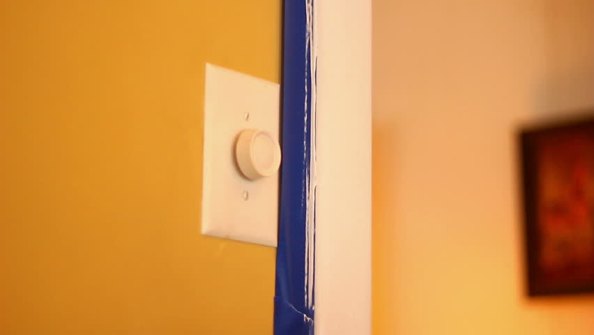 A painter removes blue painter's tape after painting trim in a house.  With