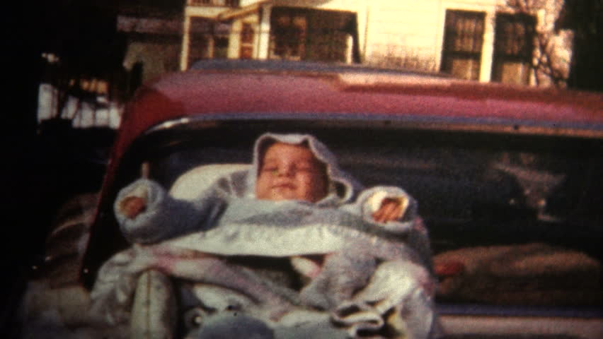 LOUISVILLE, KENTUCKY - AUGUST 1966 Baby sleeping in a carrier on the trunk of a car, not to the safety standards of the 21st century.