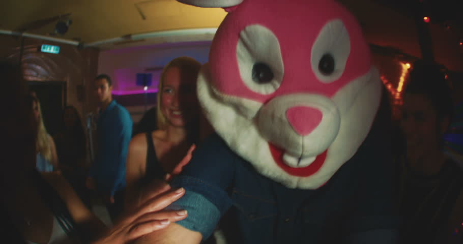 Group of friends at a party with one wearing a plush rabbit head