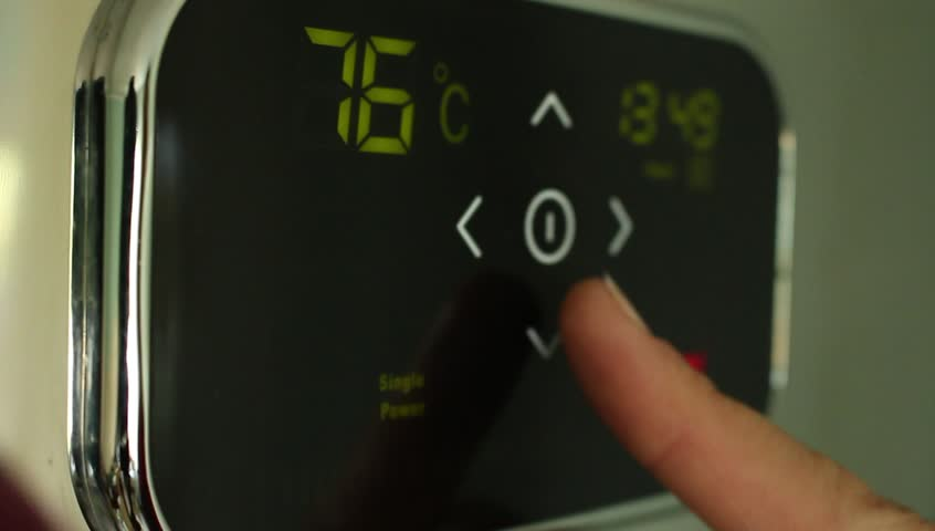 Turning down the temperature. Touch panel closeup. Electric Water Heater. Setting the temperature. Digital display.