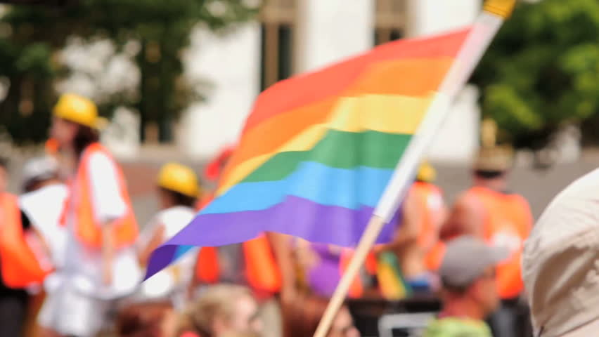 A Rainbow flag waves as a float of excited gay pride supporters pass by in the background. slow motion. Symbol of LGBT GLBT transgender rights love equality and freedom
