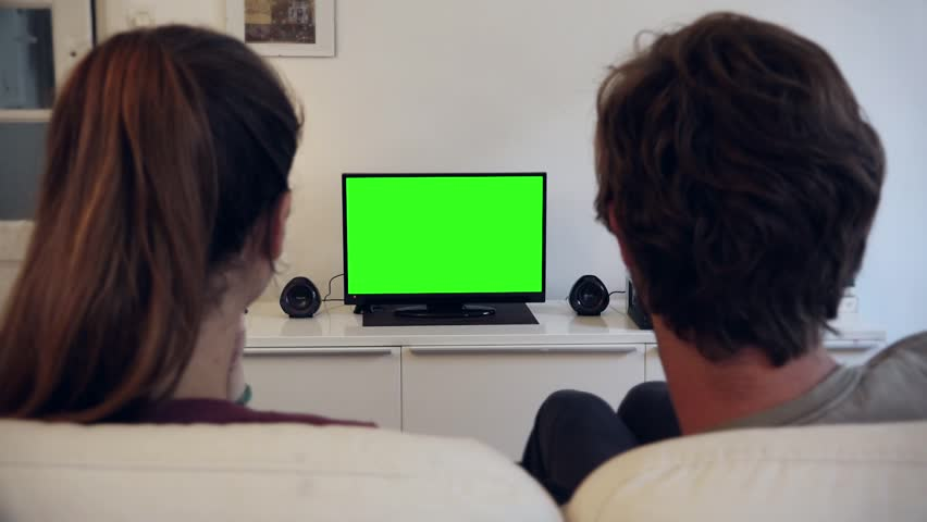 Green Screen TV Couple - Full HD. PARIS, FRANCE - 28 JULY 2015; Couple watches television with green screen in living room / shot behind model's