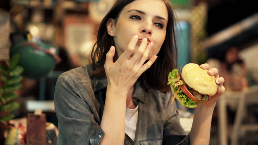 Young woman eating fast food, hamburger and french fries in cafe