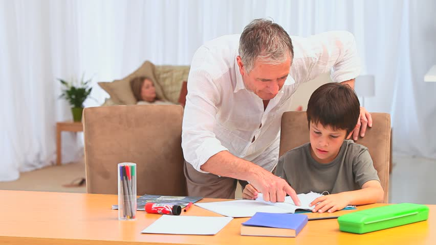 Boy Sitting At The Table Doing His School Homework Stock Photo     A child of primary school age do homework  The boy does his homework at his