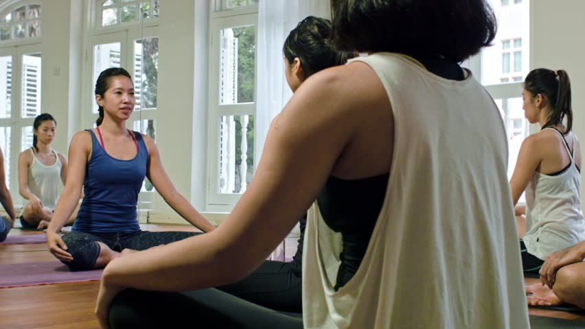 Asian yoga instructor leading prayer pose for meditation at the end of practice