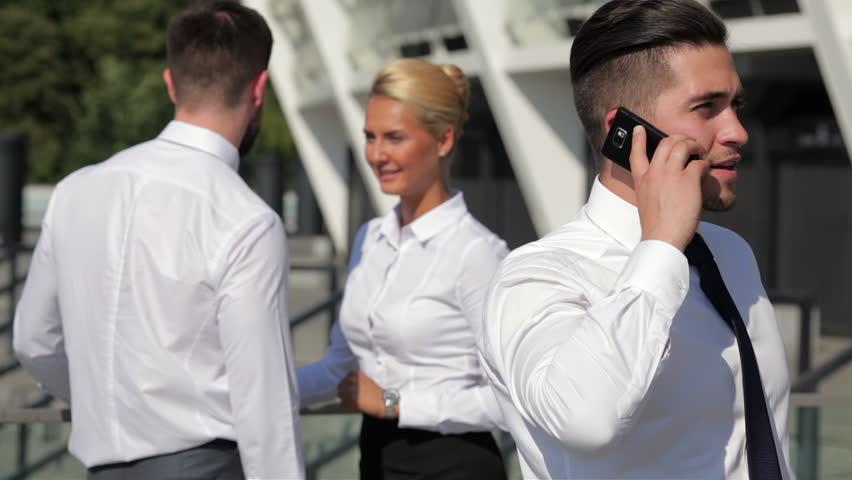 Three colleagues having conversation outdoors | Shutterstock HD Video #11237813