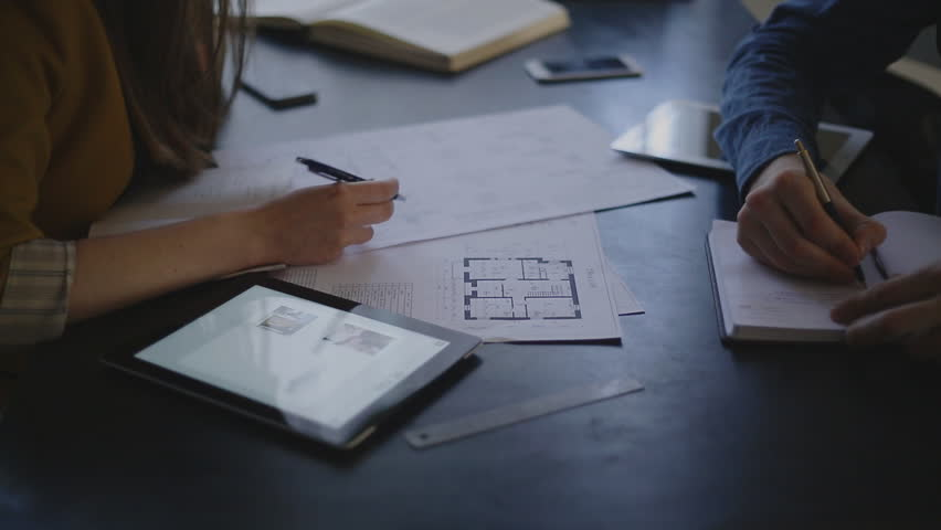 Video customer and the executor of the order for the construction sit opposite each other and discuss the subject of the order, are actively working with papers, drawings. each has its own subject for   Shutterstock HD Video #11360120