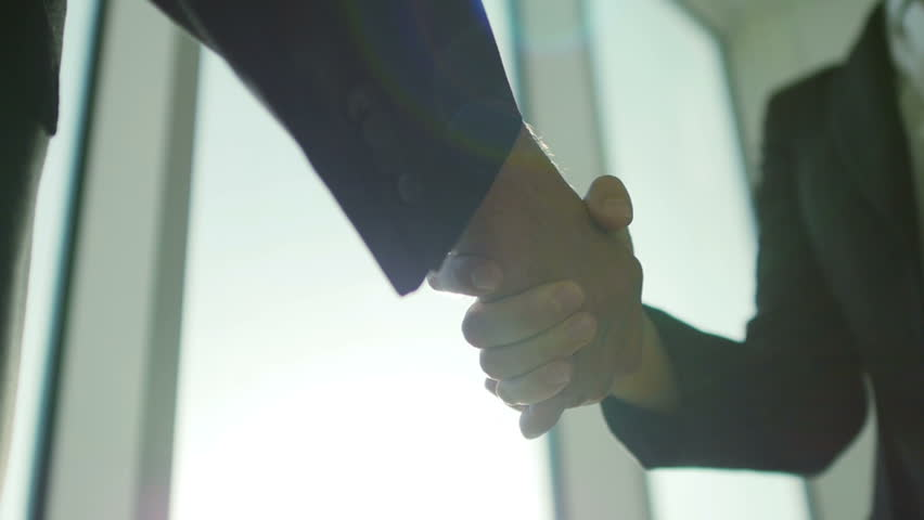 Two business partner shake hands when meeting. In slow motion