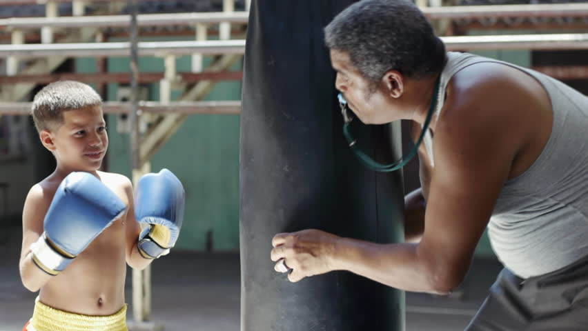 Sport activity, martial arts, young people and combat training, children practice in extreme sports in fitness gym. Hispanic boy fighting in ring, latino child punching at bag, boxing with trainer