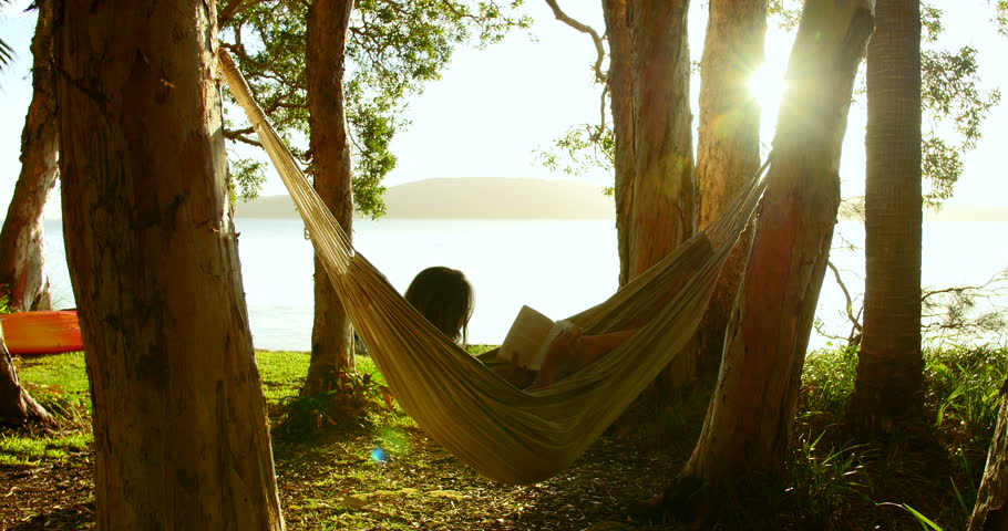Woman relaxes reading book in hammock, swaying gently, in wood on beach at sunset. Sun breaks through trees