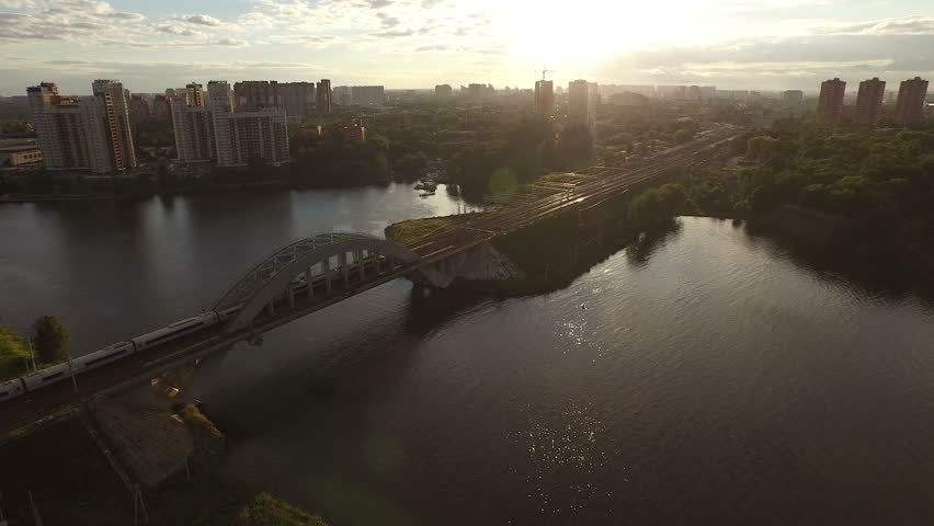 Fast train rides through the iron bridge over the river in Moscow at sunset | Shutterstock HD Video #11711312