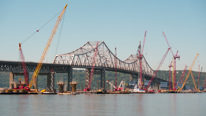 (Time-lapse/Zoom-in) Barge mounted cranes work on construction of the new Tappan Zee Bridge as traffic crosses the existing Tappan Zee Bridge on September 15, 2015 in Tarrytown. | Shutterstock HD Video #11728460