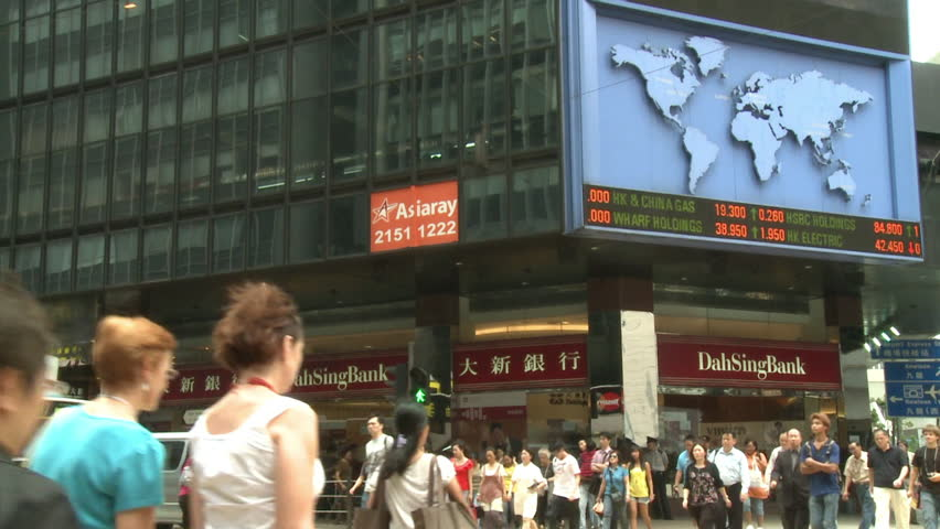 Hong Kong, China - July 2009: Traffic and people passing by a board showing the latest stock market information on a ticker tape. Downtown Hong Kong.