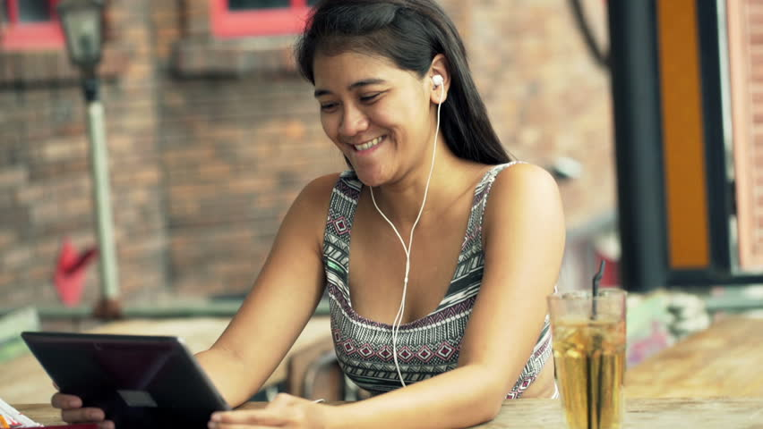 Happy, young woman watching movie on tablet computer sitting in cafe  | Shutterstock HD Video #11814422