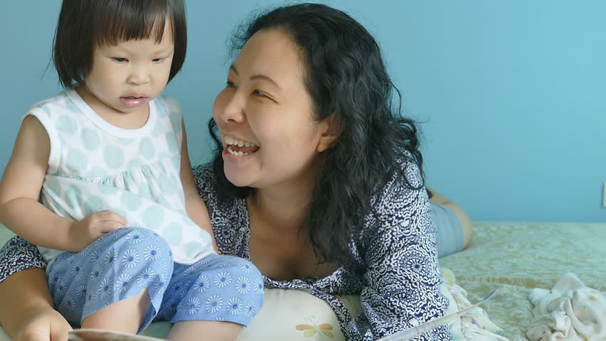 Asian mother telling a story to her baby in the bedroom    Shutterstock HD Video #11843207
