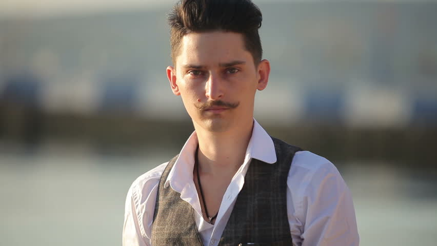 a young man with a mustache looking at you #11880524