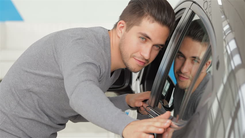 A man inspects his new car color. Auto business, car sale, technology and people concept - happy male with car dealer in auto show or salon. Young man with a salesman in a motor show. | Shutterstock HD Video #11918810