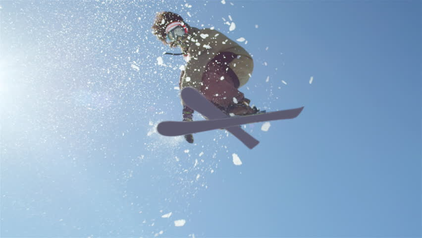 SLOW MOTION CLOSEUP: Freestyle skier jumping big kicker and flying over the sun in snowy mountains   Shutterstock Video #12010307