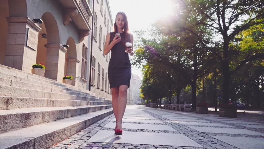 Attractive business woman in red high heeled shoes walking in the city, drinking coffee and using a smartphone in the morning. Steadicam stabilized shot in Slow motion. Lens flare. | Shutterstock HD Video #12063527