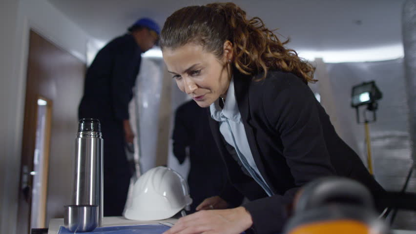 4k Confident female engineer looking at blueprints on construction site. Shot on RED Epic. | Shutterstock HD Video #12104336