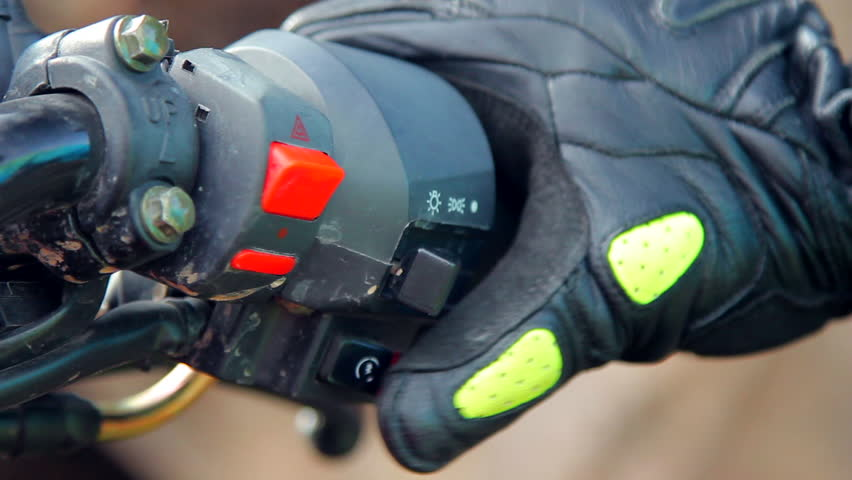 Closeup shot of a right grip of a motorcycle. Biker is pressing start button and bending the throttle.