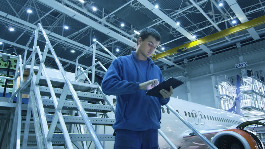 Aircraft maintenance mechanic is going down the stairs while using tablet and greeting his colleague a the bottom in a hangar. Shot on RED Cinema Camera in 4K (UHD).