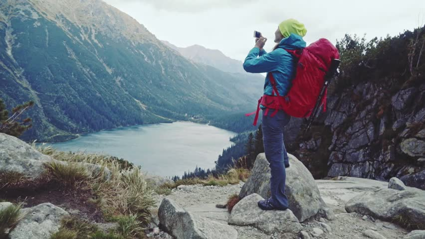 Hiker woman taking picture with smart phone from mountain peak with lake view. Tourist using photo app, touching screen. Stabilized Slow Motion 120 fps. Epic Steadicam shot. Misty Mountains Series.