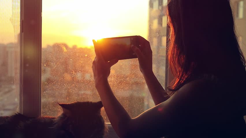 Young woman in headphones relaxing with her lovely Maine Coon cat at window taken pictures of blurred city background at sunset in slowmotion. 1920x1080 | Shutterstock HD Video #12208163