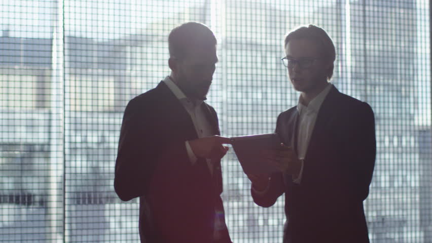 Two businessman are using a tablet while talking in a garage parking lot. Shot on RED Cinema Camera in 4K (UHD).