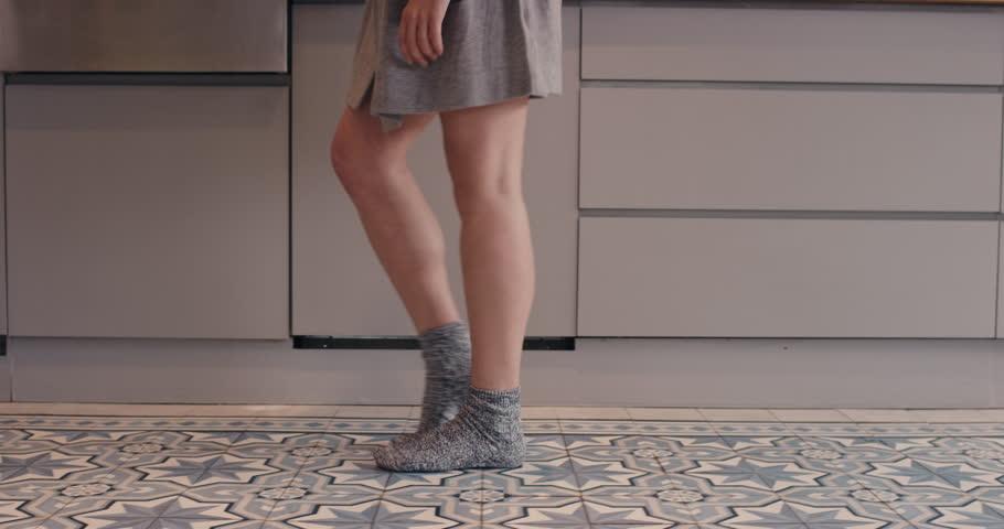 Dancing woman in kitchen moonwalk silly wearing pajamas at home having fun