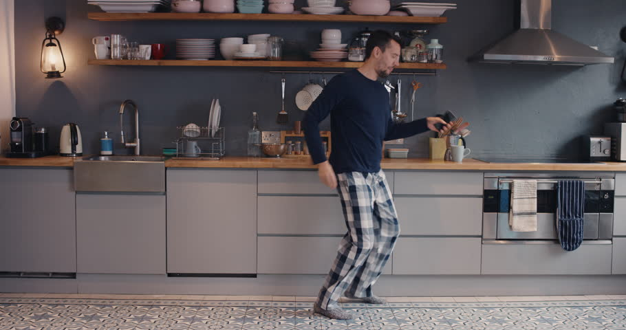 Happy young man dancing in kitchen wearing pajamas in the morning listening to music on smartphone and coffee at home | Shutterstock Video #12273485