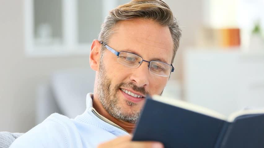 trendy eyeglasses ysgm  40-year-old man relaxing in sofa reading book