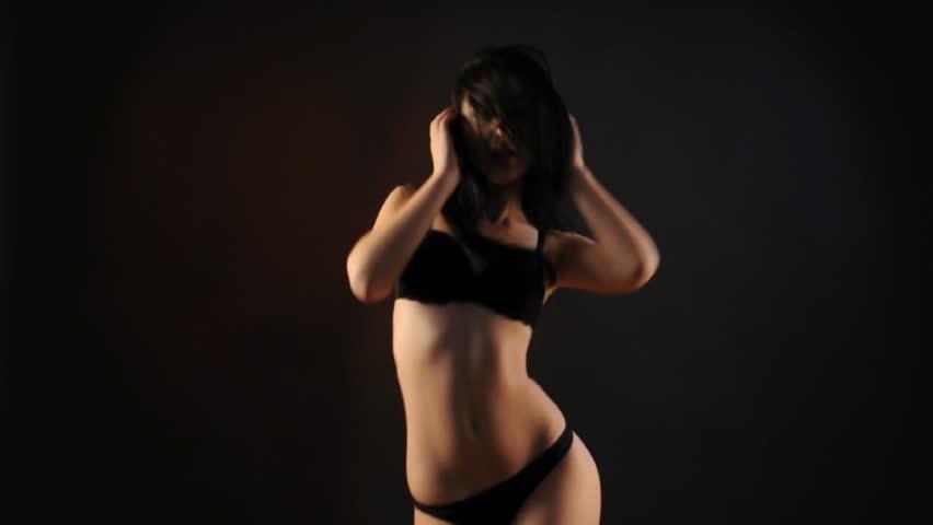 sexy brunette in black lingerie dancing in the dark. Medium long shot