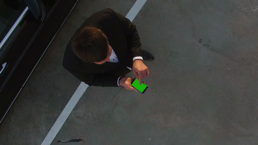 Zoom Out from Businessman Green Screen Phone to...