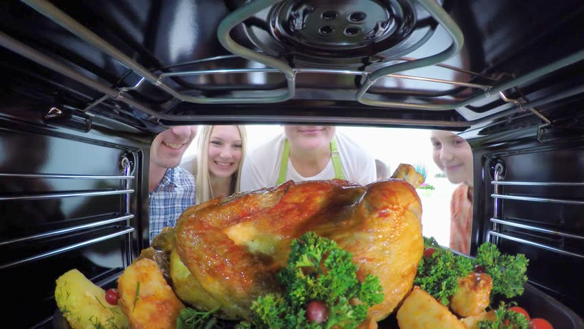 Happy big family with children cooking chicken in the oven together. Holiday dinner at home. 4K POV video footage