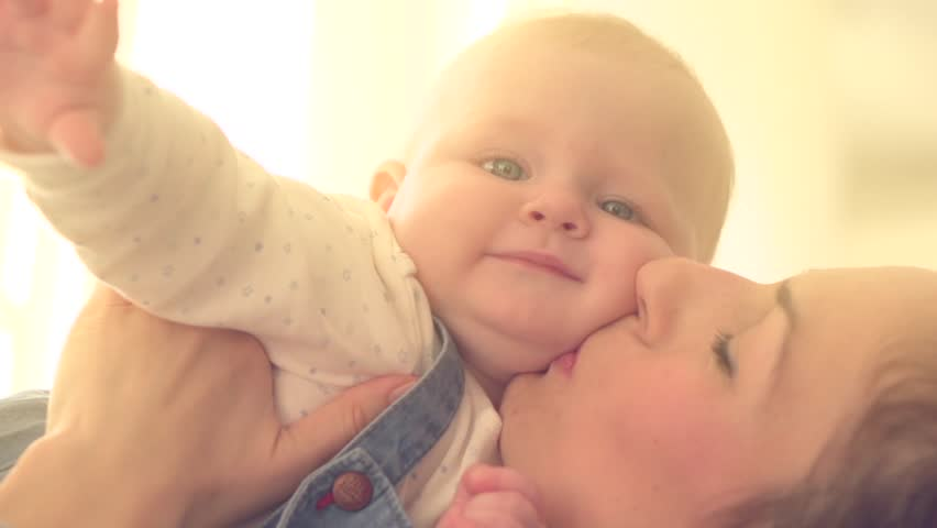 Mother and Baby smiling together. Love. Happy cheerful family Mom and Baby girl kissing and hugging at home. Beautiful healthy mother and little daughter. Maternity concept. Parenthood. Slow motion
