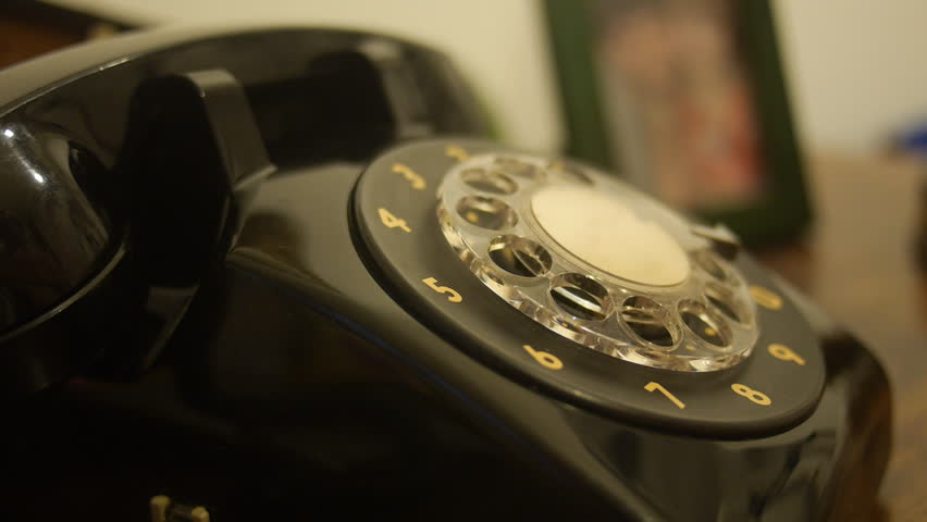 Close-up view of hand dialing a number on old black telephone from 1970.